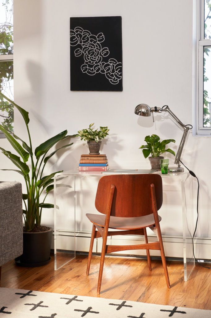 Bird of Paradise next to desk and chair in living room with air conditioning vent